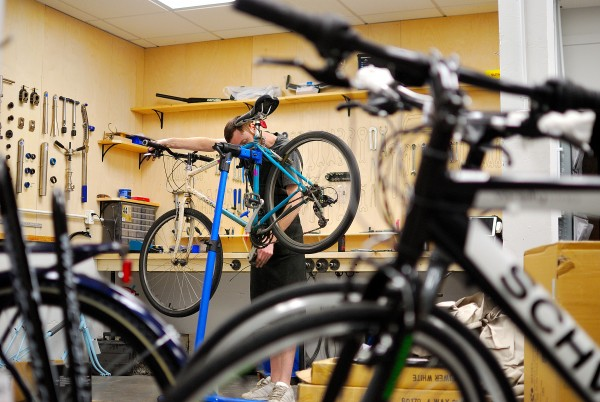 Assistant Manage Michael Glenn works on a bike at Neutral Cycle on 5th Street in Champaign, IL. Photo by Alyssa Abay